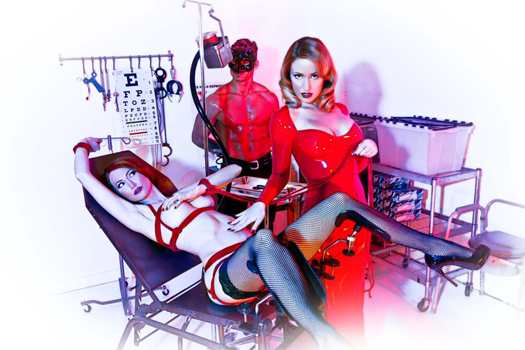 Naked brunette strapped to a medical table, while a blonde in a bright red dress caresses her stomach.