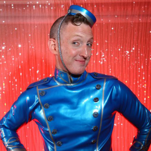 Kip dressed in a blue latex bellhop outfit.